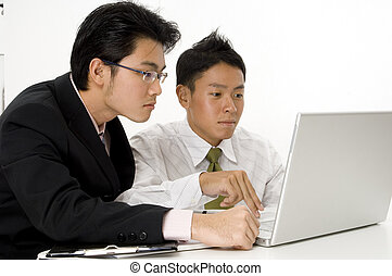 Men Working On Computer - Two asian businessmen working on a...