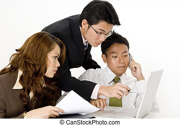 Working Business Group - A busy team of three working on...