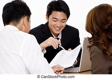 Helpful Advice - A young employee helps a couple with a form