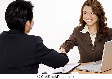 Business Deal - A smiling businesswoman shakes hands with a...