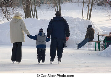 Family on a skating rink - Skating in solar winter day on...
