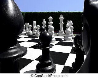 Chess in a garden - Human size chess figures in a garden on...