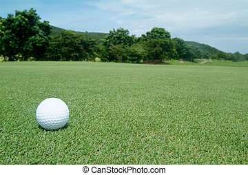 Golf-ball on green with scenery in the background