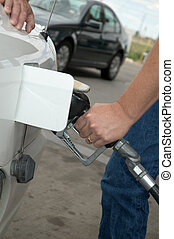 Those gas prices! - A man filling up his car with gas with a...