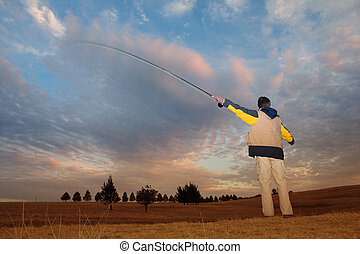 Flyfishing 2 - A fly fisherman casting a line in Dullstroom,...