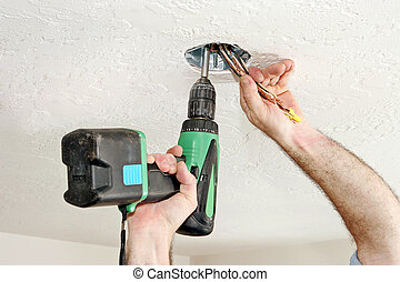 Electrician With Drill - An electricians hands using a drill...