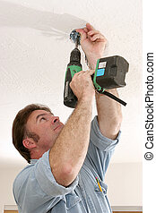 Electrician Installing Fan Box - An electrician using a...