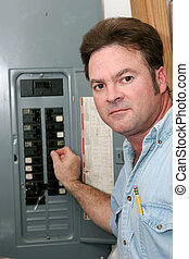 Electrician At Breaker Panel - An electrician at an...