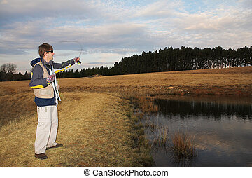 Flyfishing 12 - A fly fisherman casting a line in...