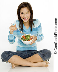 Eating Salad - A young asian woman sitting on the floor with...