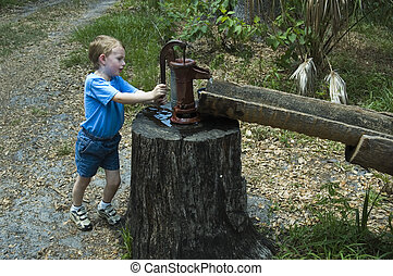 Boy pumping water - Young boy pumping water from an old hand...