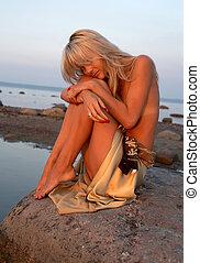 sad topless girl on the rock