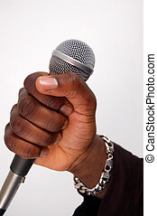 Speech - This is an image of a hand on a microphone.