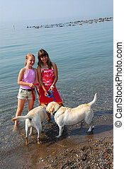 Two girls playing with dogs on a beach