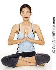 Yoga Meditation - A young asian woman meditates with her...