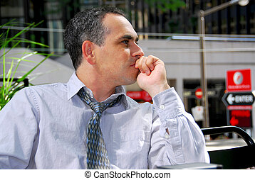 Businessman thinking - Businessman sitting in outdoor cafe...