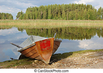 Red rowing boat - Rowing boat on shores of a Finnish lake