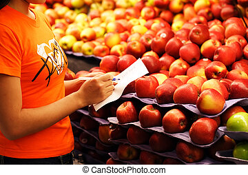 Grocery shopping - A woman shopping for apples at a grocery...
