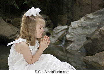 Little girl praying outside