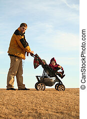 father with stroller - active young dad with his child in a...