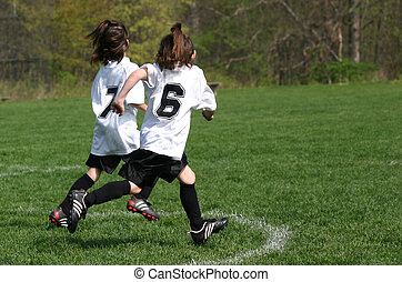 soccer duo - girls youth soccer players running across field