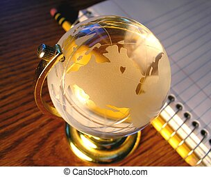 Studying Globally - A glass globe with a spiral notebook in...