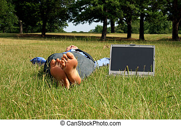 Outdoor Businessman - Barefoot man lying in grass takes a...