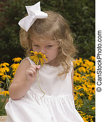 Spring time - Girl smelling a flower - black-eyed suzies