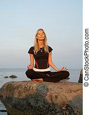 meditation at the seashore - Fit girl meditating at the...