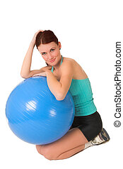 Gym #58 - Woman sitting next to a blue gym ball.
