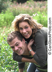 Piggyback ride - Cute young couple playing piggyback ride in...