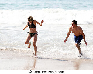 Playing on the beach - Young couple playing on the beach