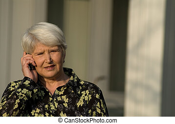 on the phone - elderly woman outdoors with cell phone