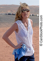 Windy day at the beach - woman standing on a beach with wind...