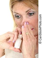 Use Nasal Spray Hand - Woman demonstrates using nasal spray...