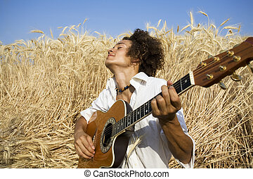 playing guitar - cool guy laying in a cornfield playing...