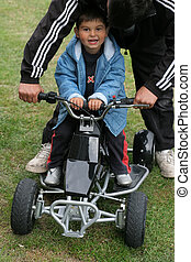 Learning to Race - Little boy on a mini moto quad bike with...