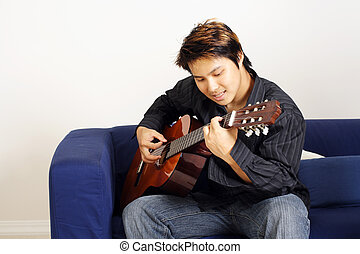Guitar player - A handsome man playing a guitar