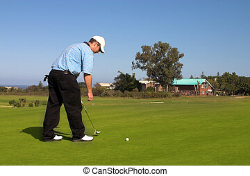 Golfer picking up the ball on the green Copy space