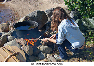 Campfire girl - Teenage girl feeding a campfire