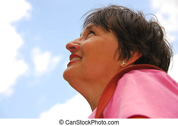 Optimistic woman looking up blue sky