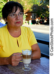 Mature woman coffee - Mature woman in outdoor cafe with...
