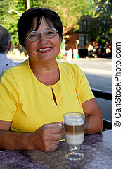 Mature woman coffee - Smiling mature woman in outdoor cafe...