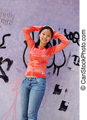 Beautiful young Korean woman in urban setting with graffiti