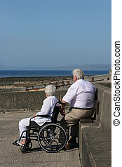 Togetherness - Disabled elderly woman in a wheelchair...