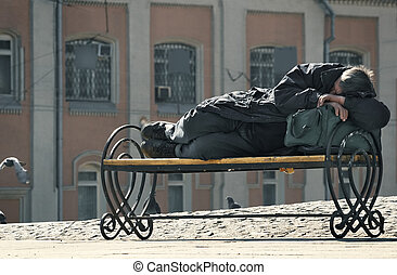 Homeless - The homeless sleeps on a bench in beams of the...