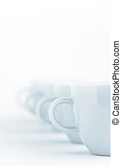 Line of cups on a white cloth