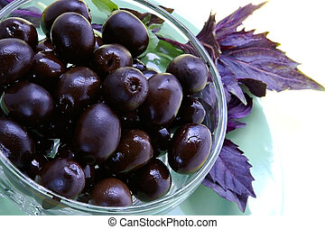 Black olives and basil-dishes with appetizing snack