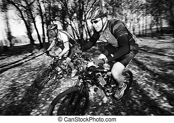 Mountainbiking 3 - Panning shot of two mountain bikers,...