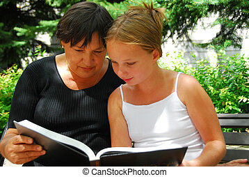 Generations book - Grandmother and granddaughter reading a...
